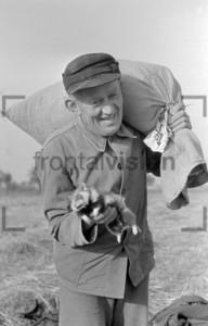 Bauer auf dem Feld mit Sack und Meerschweinchen