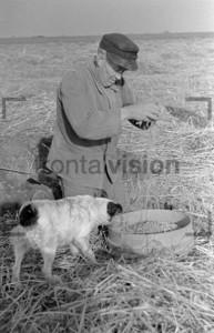 Bauer auf dem Feld mit Sack und Hund